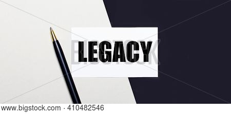 On A Black And White Background Lies A Pen And A White Card With The Text Legacy.