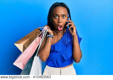 Young african woman holding shopping bags and speaking on smartphone afraid and shocked with surprise and amazed expression, fear and excited face.