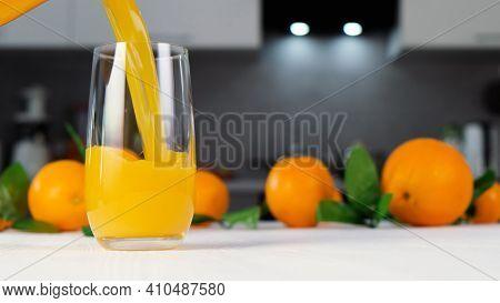Orange Juice Pouring Into Glass On White Table. Citrus Juice Splash