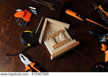 Various Repair Tools And Model Of House. Repair Tool Kit On A Wooden Background