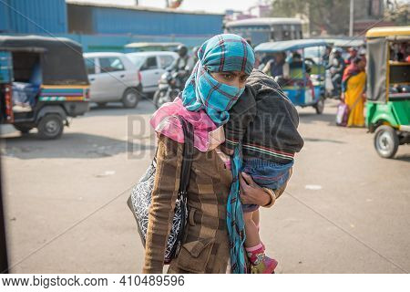 Jaipur, India. 09-05-2018. Mother Carrying Her Son While Walking At The Local Fruits And Vegetables