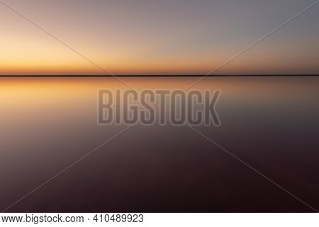 Tranquil minimalist landscape with smooth surface of the pink salt lake with calm water with horizon with clear sky in sunset time. Simple beautiful natural calm background
