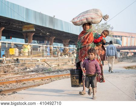 Jaipur, India. 09-05-2018. Mother Carrying Her Child And In Her Arms As Well As Some Belongings On H