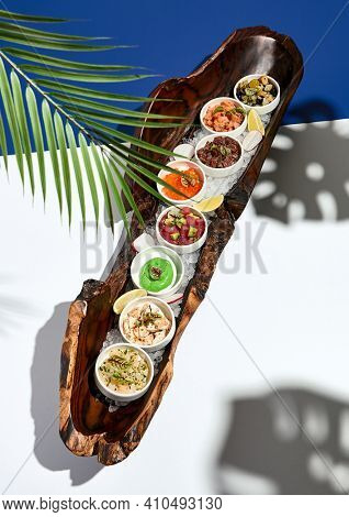 Restaurant plate - Tartar wooden dish with dips. Gourmet food plate on white table with blue wall. Day sunlight with hard shadow of palm leaves. Tropic, summer or spring food concept