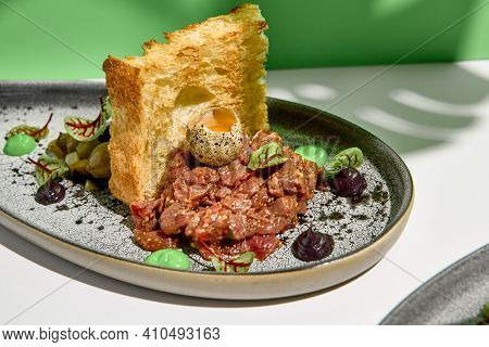 Beef tartar with egg and toast bread. Meat restaurant appetizer on white table with green wall. Day sunlight with hard shadow of monstera palm leaves. Summer or spring restaurant food concept