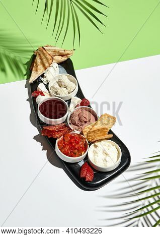 Wine snack food on wooden platter. Italian gourmet appetizer on white table with green wall. Day sunlight with hard shadow of monstera palm leaves. Summer or spring restaurant food concept
