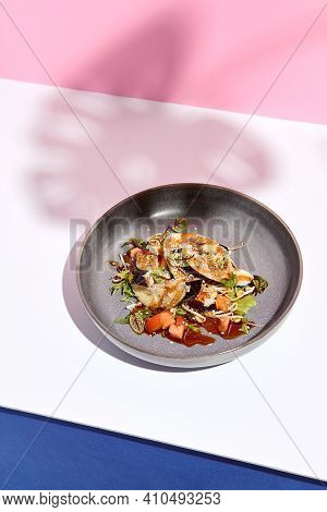 Eggplant restaurant appetizer plate. Restaurant appetizer food plate on white table with pink wall. Day sunlight with hard shadow of monstera palm leaves. Summer or spring restaurant food concept