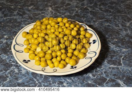 Tinned Green Peas On A White Plate. Peas For Food. Dark Blue Background.