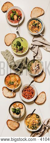 Flat-lay Of Vegetarian Creamy Homemade Soup With Bread Slices Over White Plain Table Background, Top