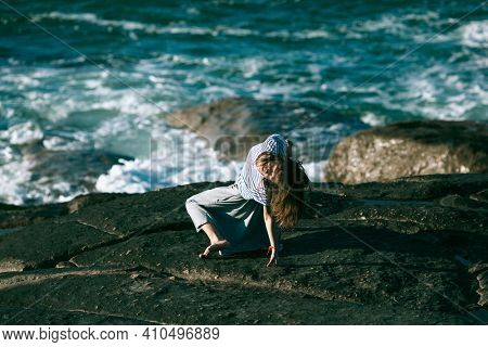 An dancer woman is engaged in choreography on the rocky coast of Atlantic ocean.