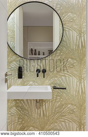 Bathroom With Wallpaper With Plant Leaves Texture, Small Wash Basin And Round Mirror. Minimalist Int