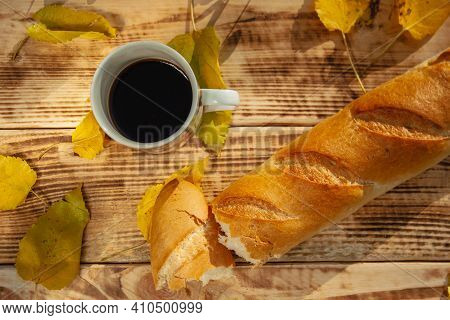 A Cracked, Crunchy Baguette And Foliage Lie On A Wooden Background, Next To A Mug Of Coffee. Top Vie