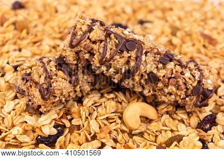 Granola Bars On The Background Of Scattered Granola. Healthy Food Concept.