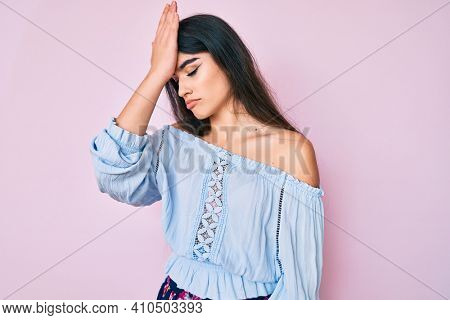 Brunette teenager girl wearing casual clothes surprised with hand on head for mistake, remember error. forgot, bad memory concept.
