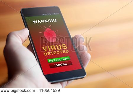 Closeup Of Male Hand Holding Modern Mobile Phone With Red Antivirus Warning Screen Showing Text