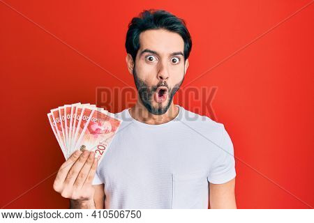 Young hispanic man holding 20 israel shekels banknotes scared and amazed with open mouth for surprise, disbelief face