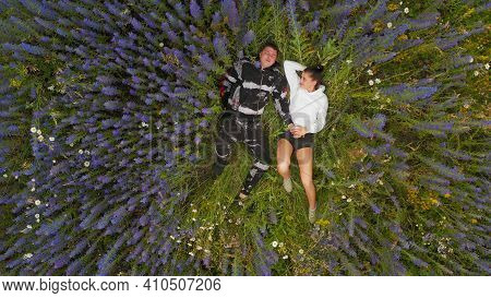 Handsome Guy And Girl In Blooming Flowers. A Guy And A Girl In Cyanosis Flowers. A Loving Guy And A
