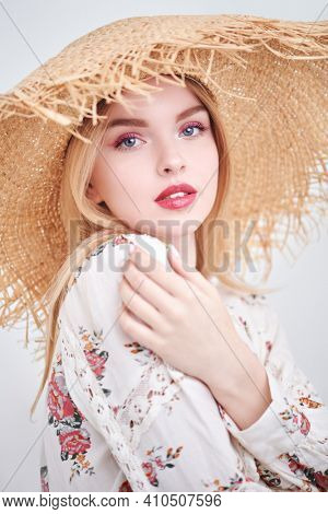 Gentle blonde girl in a straw hat and a summer blouse poses on a white background. Light fresh makeup in pink colors. Spring and summer fashion.