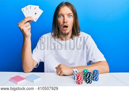 Handsome caucasian man with long hair playing poker holding cards scared and amazed with open mouth for surprise, disbelief face