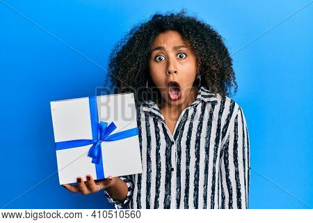 Beautiful african american woman with afro hair holding gift scared and amazed with open mouth for surprise, disbelief face