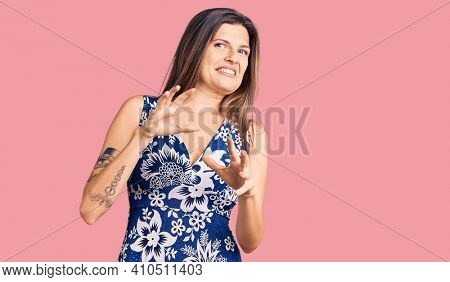 Beautiful caucasian woman wearing summer dress disgusted expression, displeased and fearful doing disgust face because aversion reaction. with hands raised