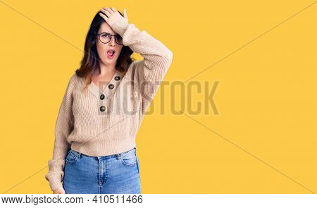 Beautiful young brunette woman wearing casual clothes and glasses surprised with hand on head for mistake, remember error. forgot, bad memory concept.