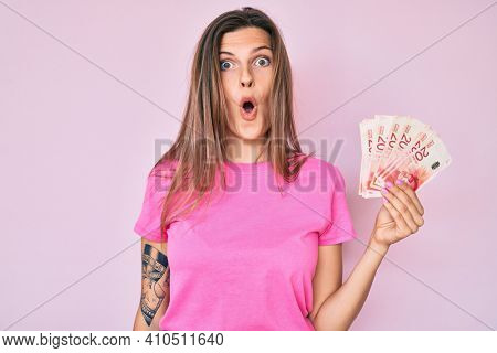 Beautiful caucasian woman holding israel shekels scared and amazed with open mouth for surprise, disbelief face