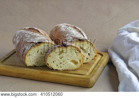 Bread Loaf, Cut Into Pieces, On Wooden Cutting Board. Baked Bread And Dish Towel On Craft Paper, Hom