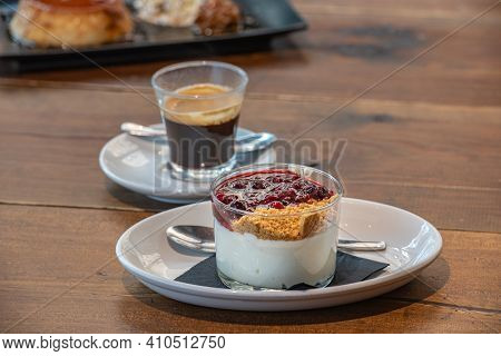 Flan Casero And Cheesecake Served In A Glass With A Berry Sauce.