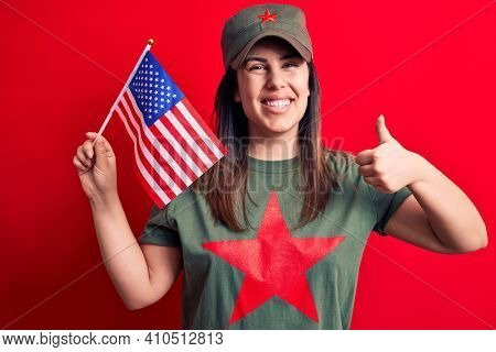 Beautiful woman wearing t-shirt with red star communist symbol holding united states flag smiling happy and positive, thumb up doing excellent and approval sign