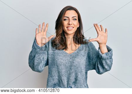 Young brunette woman wearing casual winter sweater showing and pointing up with fingers number ten while smiling confident and happy.