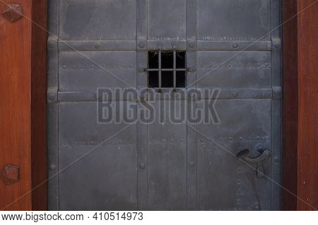 Detail Of A Metal Door. There Is A Window And A Handle On The Door. There Is A Wooden Door Frame Aro