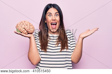 Young beautiful brunette woman asking for memory healthy and mental care holding brain celebrating achievement with happy smile and winner expression with raised hand