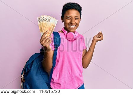 Young african american girl wearing student backpack holding norwegian krone banknotes screaming proud, celebrating victory and success very excited with raised arm