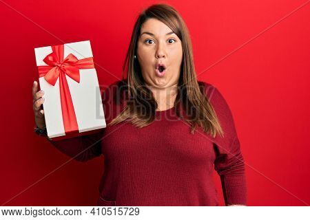 Beautiful brunette plus size woman holding gift scared and amazed with open mouth for surprise, disbelief face