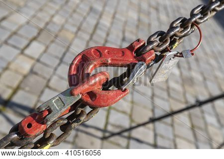 The Red Pulley Connects And Tightens The Chain. There Is A Sidewalk Under The Pulley.