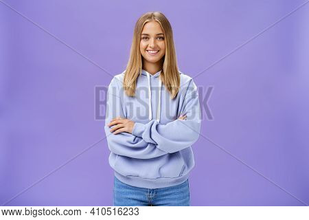 Portrait Of Charming Charismatic European Woman With Tanned Skin In Trendy Over-sized Hoodie Crossin