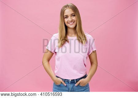 Charming Pleasant Woman With Chubby Face And Fair Hair In Casual T-shirt Smiling Broadly Holding Han