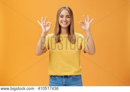 Optimistic Charming Woman With Fair Hair And No Make-up In Yellow T-shirt Showing Okay Or Approval G