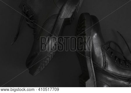Fashionable Youth Black Leather Boots On Black Background Flat Lay Top View. Stylish Womens Mens Uni