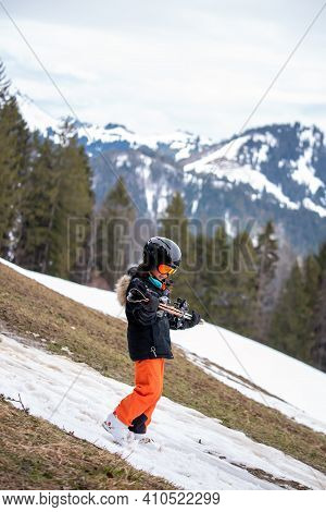 Problem Of Global Warming And Winter Skiing. One Asian Walking Downhill With Ski In Hands. Climate C