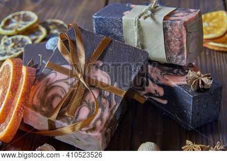 Scented Organic Dark Handmade Soap, Scented Spices And Orange Slices On A Brown Wooden Countertop.