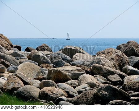 Rocky Shoreline With Sailboat In The Background. Coast Of Hammonasset Beach State Park In Madison. C