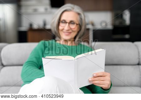 Thoughtful Happy Mid-aged Senior Woman In Glasses And Green Jumper Sitting On The Couch, Resting And