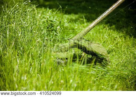 mowing a green lawn with a lawn mower
