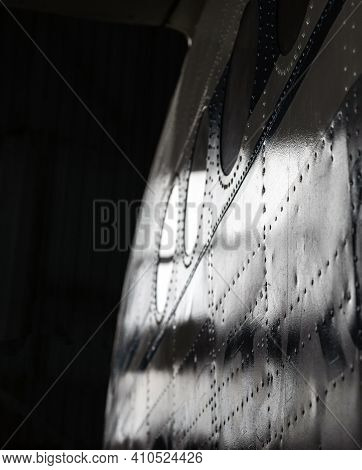 Part Of The Aluminum Fuselage Of The Aircraft With Rivets And Portholes. Selective Focus.