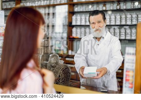 Smiling Friendly Senior Bearded Man Pharmacist, Standing At The Counter In Old Pharmacy, Offering Me