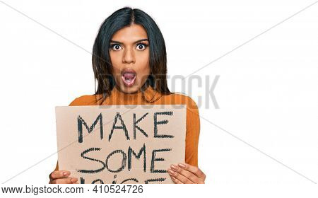Young latin transsexual transgender woman holding make some noise banner scared and amazed with open mouth for surprise, disbelief face