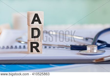 The Word Adr Is Written On Wooden Cubes Near A Stethoscope On A Paper Background. Adr - Short For Ad