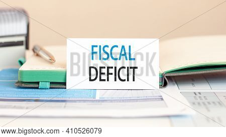 White Paper Card With Text Fiscal Deficit To The Background Of A Notebook, Pen, Stamp In The Backgro